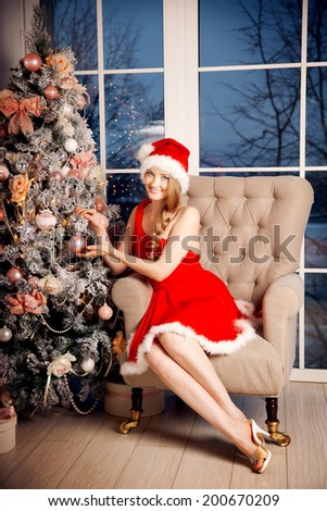 Young beautiful smiling santa woman near the Christmas tree. Fashionable luxury girl celebrating New Year. Beauty luxury trendy blonde.   - stock photo