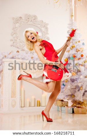 Young beautiful smiling santa woman near the Christmas tree with bunny. Fashionable luxury  girl celebrating New Year with electric guitar. - stock photo