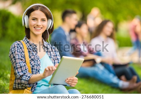 Young beautiful smiling student sitting on the lawn at park and listen to music. - stock photo