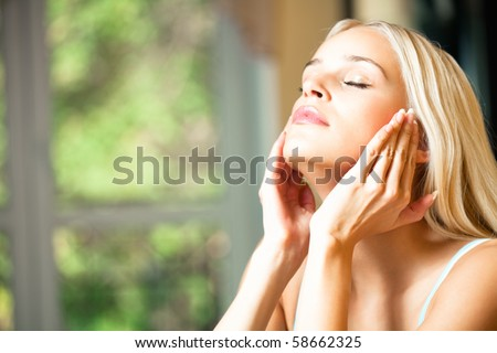 Young beautiful smiling woman applying creme