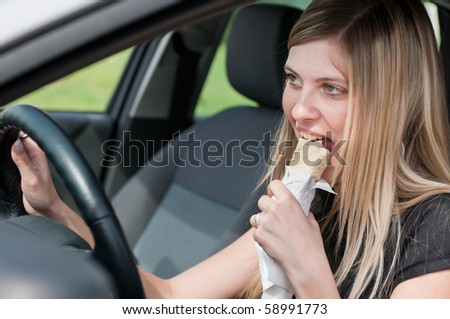 Young beautiful smiling woman driving car and eating fast food - portrait through side window - stock photo