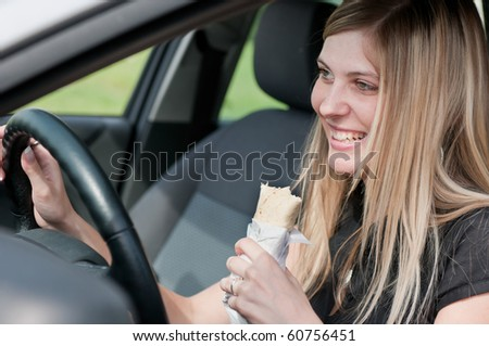 Young beautiful smiling woman driving car and eating fast food - portrait through side window