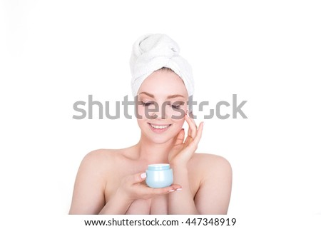 Young beautiful smiling woman holds soft skin in her face and shows new cream with closed eyes and white towel on her hair after bath - stock photo
