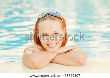 Young beautiful smiling woman in bikini in warm pool on resort. - stock photo