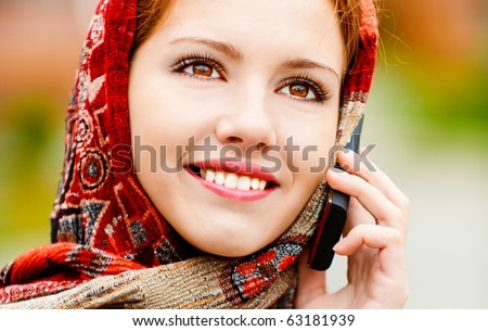 Young beautiful smiling woman in motley red headscarf talks on cellular telephone, against city structures. - stock photo