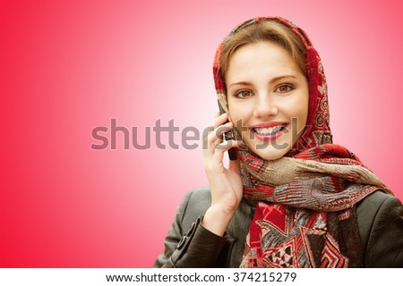 Young beautiful smiling woman in motley red headscarf talks on cellular telephone isolated on red background. - stock photo