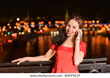 Young beautiful smiling woman in red dress talks on mobile telephone against the night Moscow Kremlin. - stock photo