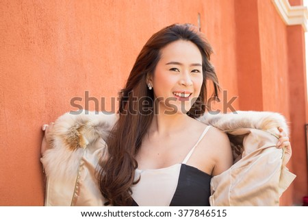 young beautiful smiling woman in sexy black and white dress taking off her fur pink jacket.  - stock photo