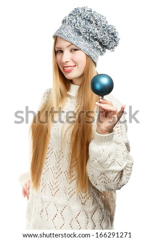 Young beautiful smiling woman in winter clothing and strange hat with blue christmas tree ball - stock photo