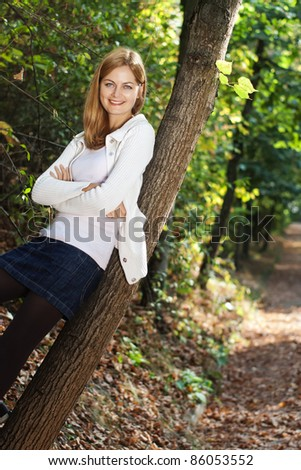 Young beautiful smiling woman leaning against tree with blurred early autumn background - stock photo