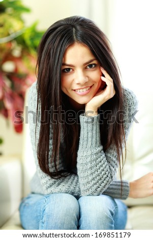 Young beautiful smiling woman sitting on the armchair at home - stock photo