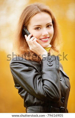 Young beautiful smiling woman talking on cell phone in autumn Park - stock photo