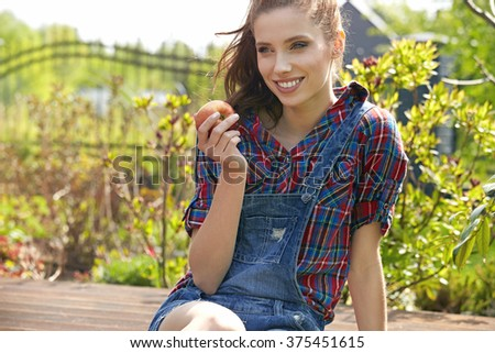Young beautiful smiling woman taste apple in the garden