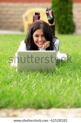 Young beautiful smiling woman using laptop on campus/home yard. Sunny day. - stock photo