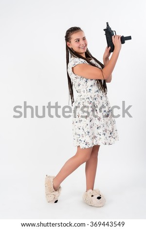 Young beautiful smiling woman with african braids aiming in target from gun - stock photo