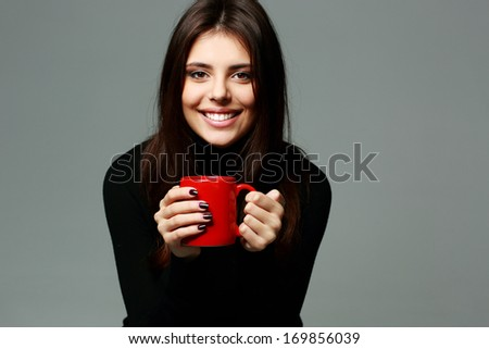Young beautiful smiling woman with cup of coffe on gray background