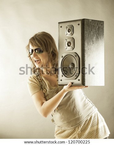 Young beautiful smiling woman with sunglasses holding big wooden speaker and listening music - stock photo