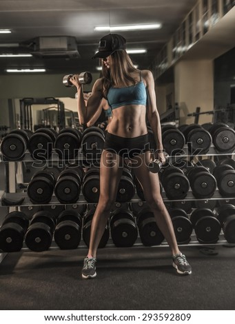 Young, beautiful, sports girl based on dumbbells shelf near mirror wall reflection of the gym. Cute slim woman look at camera Empty space for inscription Full length athlete body - stock photo