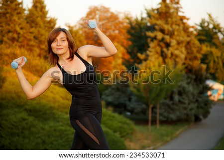 Young beautiful sports girl with dumbbells in the park on a background of trees with rough sunset. Beautiful sporty woman with dumbbell. Woman in fitness wear exercising with dumbbell, outdoors. - stock photo