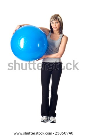 Young beautiful sportswoman standing with a fitness ball.
