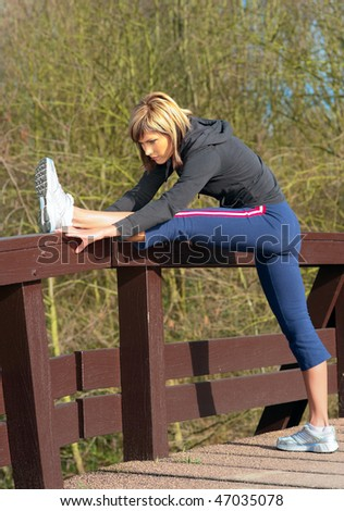 Young beautiful sportswoman stretching outdoors in a park. - stock photo