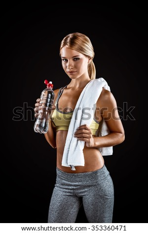 Young beautiful sporty blonde on black background. Fit sportswoman resting. Woman holding white towel and bottle of water - stock photo