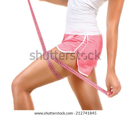 Young Beautiful Sporty Woman Measuring her Leg with a Metric Tape measure Standing Sideways  - stock photo