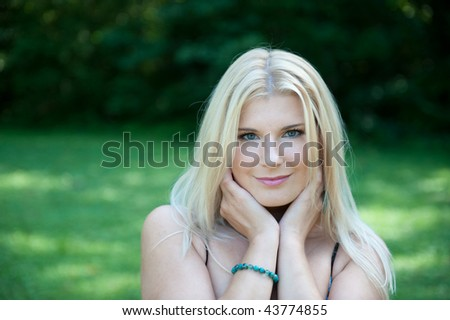 Young beautiful spring woman with healthy pure skin in a green park smiling with small daisy flower in her hair - stock photo