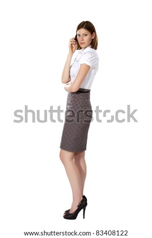 Young beautiful strict businesswoman standing aside and calling - stock photo