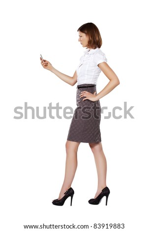 Young beautiful strict frowning businesswoman walking and using phone - stock photo