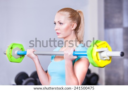 Young beautiful strong blond woman with barbell and weight plates  - stock photo