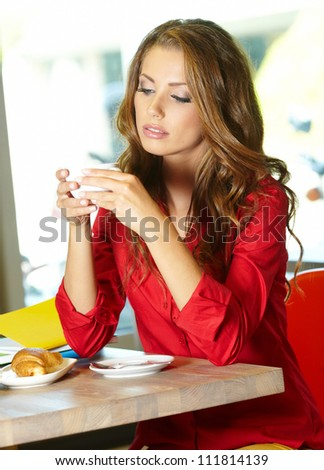 Young beautiful student girl  in the cafe - stock photo