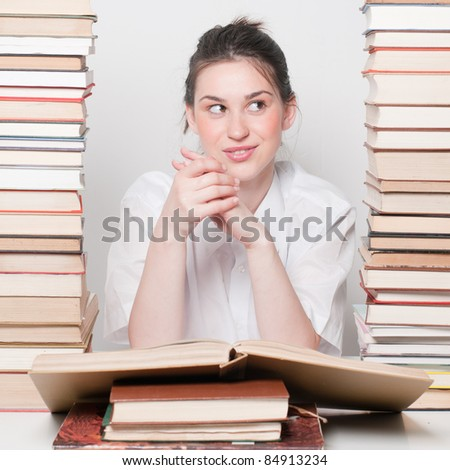 Young beautiful student girl sitting with books - stock photo