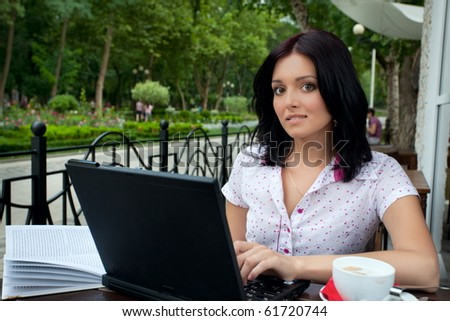 Young beautiful student girl with laptop and cup of coffee in cafe - stock photo