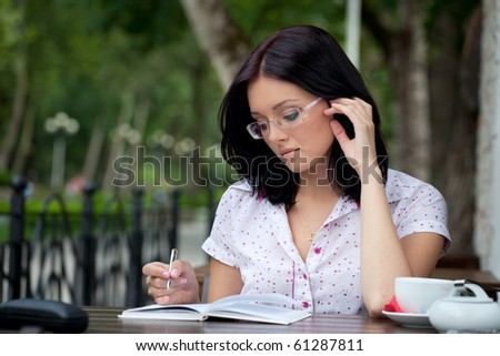 Young beautiful student girl with notepad in the cafe - stock photo