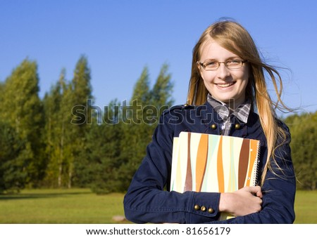 Young beautiful student girl with notes outdoor - stock photo
