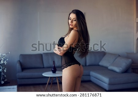 Young beautiful stunning girl with slim fit body standing in empty loft interior in minimalism style. Sensual young woman posing in sexy black lingerie - stock photo