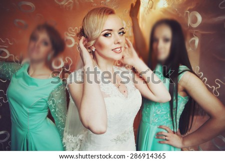 young beautiful stylish blonde bride on the background  bridesmaids in blue dresses