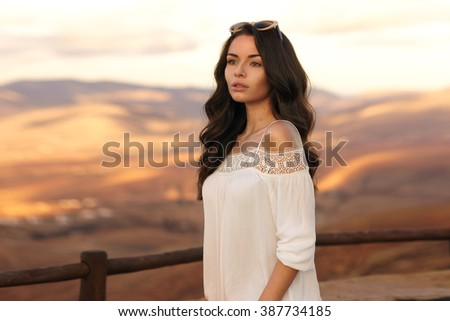 Young beautiful stylish calm girl standing against magnificent view on valley and hills at sunset. Pretty woman traveling - stock photo