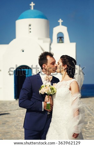 Young beautiful stylish couple newlyweds kissing outside the church on the day of their wedding on the island of Santorini, Greece. - stock photo