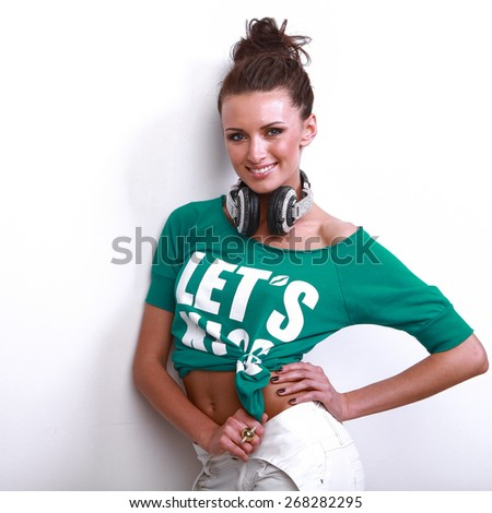 young beautiful stylish girl in a green jacket poses in front of  camera in  DJ's earphones - stock photo