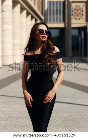 Young beautiful stylish girl posing at summer city streets on a sunny day. Stunning woman wearing black dress and sunglasses. Pretty model with long curly hair and red lips