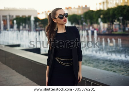 Young beautiful stylish girl walking and posing in short black dress in city near fountains. Outdoor summer portrait of young classy woman