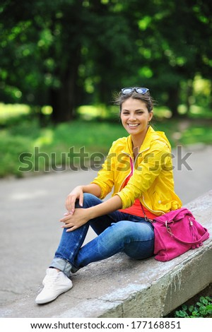 Young beautiful stylish girl with bag in a summer park - stock photo
