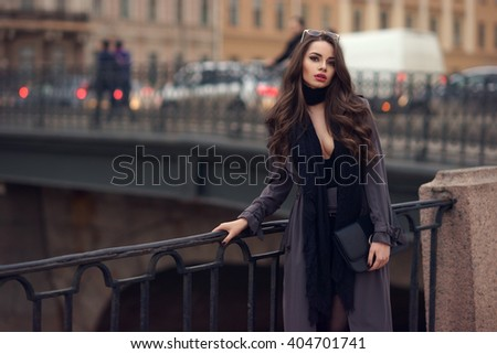 Young beautiful stylish girl with curly hair wearing black dress, scarf and gray coat standing near cast iron fence at city streets on a spring or autumn day                                - stock photo