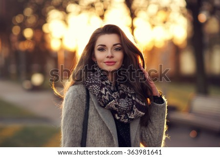 Young beautiful stylish girl with long dark hair walking outdoors in gray coat at sunset. Closeup portrait with lovely sunset light - stock photo