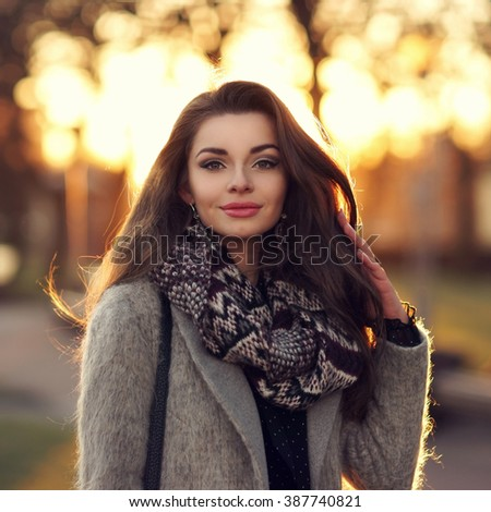 Young beautiful stylish girl with long dark hair walking outdoors in gray coat at sunset. Closeup portrait with lovely sunset light