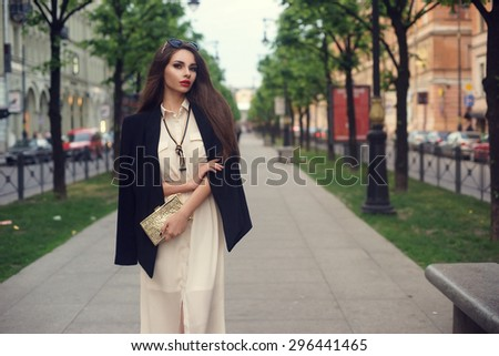 Young beautiful stylish trendy classy girl in long white dress and black blazer - stock photo