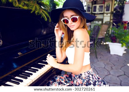 Young beautiful stylish woman,sitting on the street bench,traveling alone, enjoy her free time,wearing vintage hipster trendy outfit,street musician,singer,instrumental playing,enjoy weekends.  - stock photo