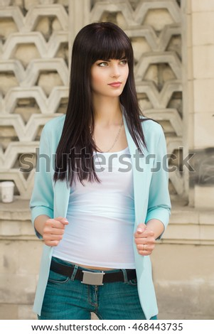 Young beautiful stylish woman with long curly hair posing at street in Turquoise jacket, and jeans.